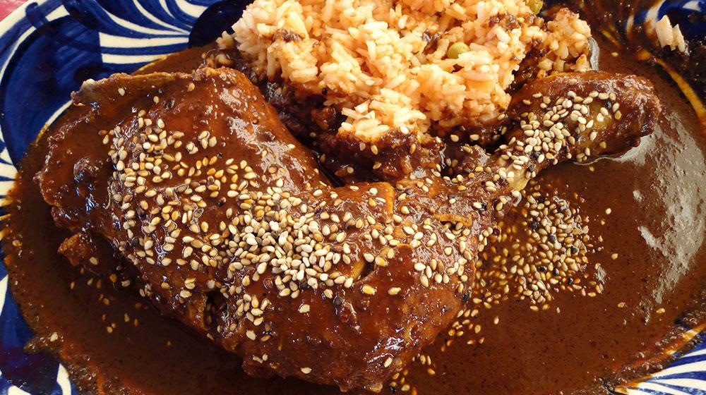 Platillo de mole poblano con piezas de diversas piezas de pollo. Puede acompañarse con arroz para su mayor disfrute.